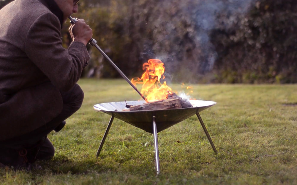 A portable stainless steel fire pit in the garden. Kevin is demonstrating how to get the fire roaring with a blowker.